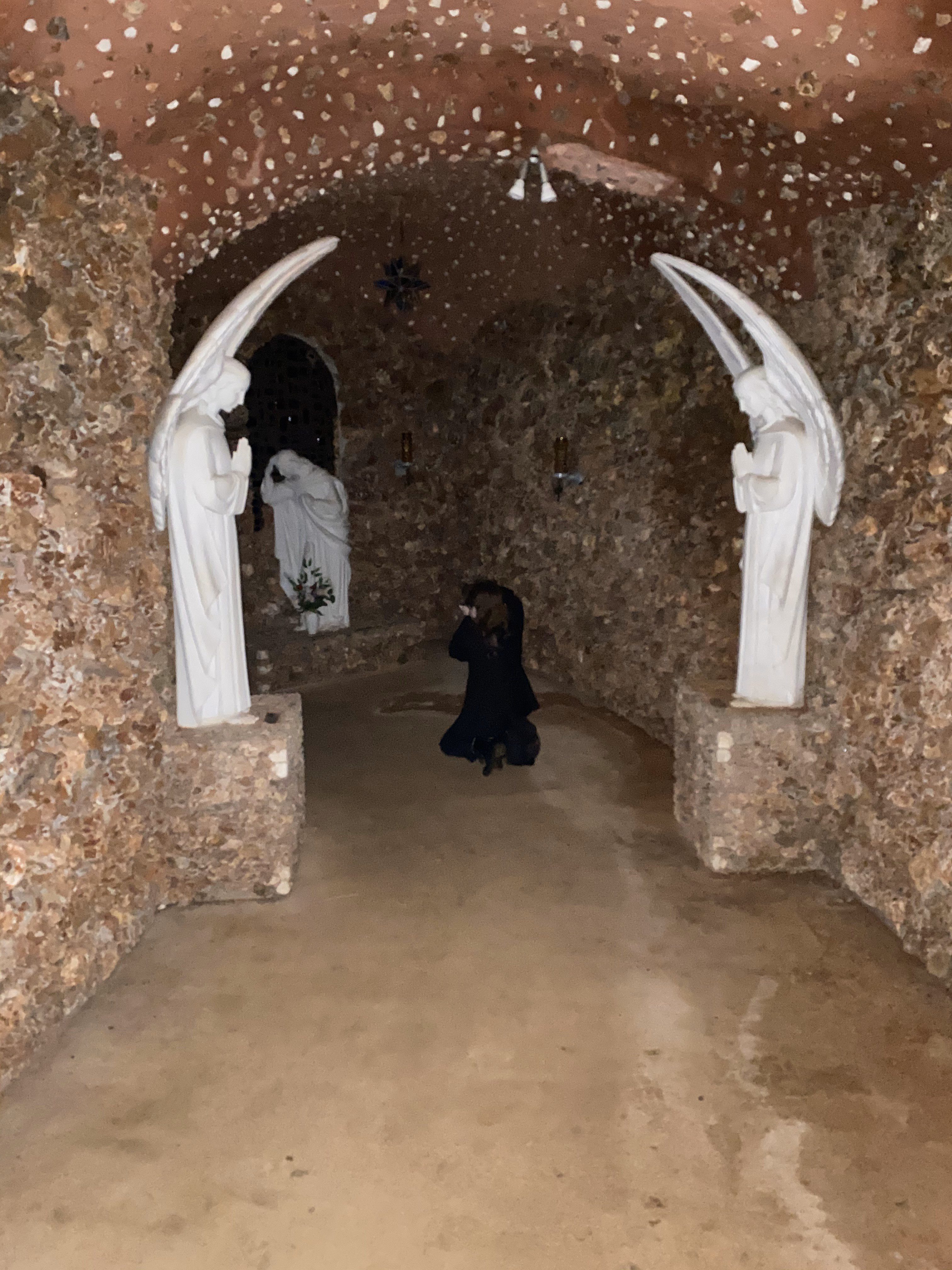 photo from behind of a man in a black suit with a brunette mullet kneeling to photograph a statue of mary. he is in an underground cave made of sponge rock, flanked on each side by two statues of angels praying.